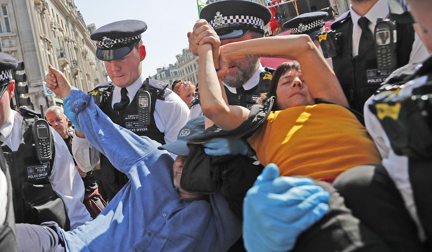 Police arrest a protester couple who are glued together by their hands, at Oxford Circus in London, Friday, April 19, 2019. The group Extinction Rebellion is calling for a week of civil disobedience against what it says is the failure to tackle the causes of climate change. (AP Photo/Frank Augstein)