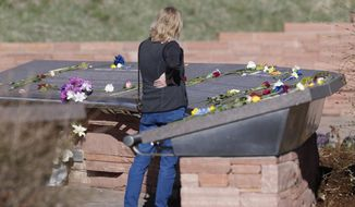 A woman looks over the stories of the slain before a vigil at the memorial for the victims of the massacre at Columbine High School nearly 20 years ago Friday, April 19, 2019, in Littleton, Colo. (AP Photo/David Zalubowski)