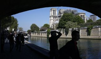 Tourists walk nearby Notre Dame cathedral, in Paris, Friday, April 19, 2019. Rebuilding Notre Dame, the 800-year-old Paris cathedral devastated by fire this week, will cost billions of dollars as architects, historians and artisans work to preserve the medieval landmark. (AP Photo/Thibault Camus)