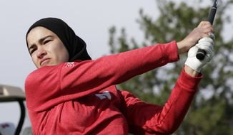 In this April 10, 2019 photo, Noor Ahmed, a member of the Nebraska NCAA college golf team, watches her shot during practice in Lincoln, Neb. Ahmed is the only golfer at the college level or higher known to wear a hijab while competing. She hopes Muslim girls are watching her and encouraged to chase their dreams in environments where they might encounter fear, uncertainty and hostility. (AP Photo/Nati Harnik)