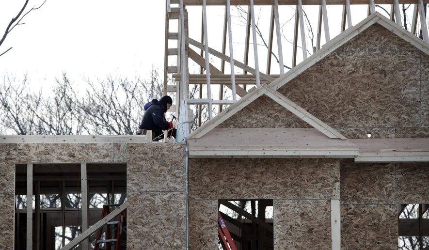 In this Jan. 23, 2019, photo, construction workers build new housing in Salisbury, Mass. On Friday, April 19, the Commerce Department reports on U.S. home construction in March. (AP Photo/Elise Amendola)