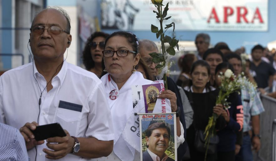 A woman carrying a photograph of Peru's late President Alan Garcia waits with others outside Garcia's political party headquarters where his wake is taking place in Lima, Peru, Friday, April 19, 2019. Garcia shot himself in the head and died Wednesday as officers waited to arrest him in a massive graft probe that has put the country's most prominent politicians behind bars and provoked a reckoning over corruption. (AP Photo/Martin Mejia)