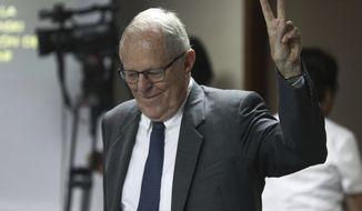 Peru's former President Pedro Pablo Kuczynski flashes a vee for victory as he returns to a court hearing to determine his release, in Lima, Peru, Monday, April 15, 2019. A judge in Peru ordered last week the detention for 10 days of the former leader as part of a money laundering probe into his consulting work for the company at the heart of Latin America's biggest graft scandal. (AP Photo/Martin Mejia)
