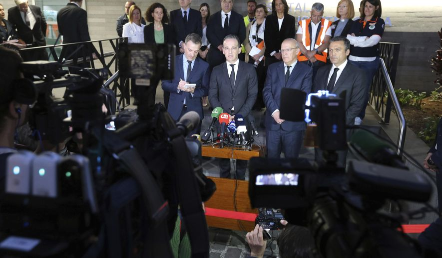 German Foreign Minister Heiko Maas, second left, Portuguese Foreign Minister Augusto Santos Silva, center, and Pedro Calado, vice president of regional government, right, address the media outside the hospital in Funchal, the capital of Portugal's Madeira Island, Thursday April 18, 2019 after visiting people injured in the bus crash. All the 29 people killed in a bus crash on Portugal's Madeira Island were German, Portugal's foreign ministry confirmed Thursday. The bus carrying 55 people, all but two of them German tourists, rolled down a steep hill after veering off the road on a bend east of Madeira's capital, Funchal, on Wednesday evening when it was still light and in fine weather. (AP Photo/Armando Franca)