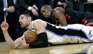 Orlando Magic's Nikola Vucevic, left, points upward after grabbing the ball away from Toronto Raptors' Serge Ibaka, right, and calling a timeout during the second half in Game 3 of a first-round NBA basketball playoff series, Friday, April 19, 2019, in Orlando, Fla. (AP Photo/John Raoux)