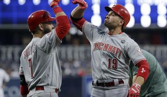 Cincinnati Reds' Joey Votto, right, celebrates with teammate Eugenio Suarez after hitting a home run during the first inning of the team's baseball game against the San Diego Padres on Thursday, April 18, 2019, in San Diego. (AP Photo/Gregory Bull)