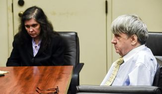 FILE - In this Aug. 3, 2018 file photo, Louise Turpin, left, and her husband, David Turpin appear in Superior Court in Riverside, Calif. The Turpins, who starved a dozen of their children and shackled some to beds, face sentencing for years of abuse. The couple is due Friday, April 19, 2019, in Riverside County Superior Court for a proceeding that is largely a formality. The couple pleaded guilty in February to torture and other abuse and agreed to serve at least 25 years in prison. (Watchara Phomicinda/The Orange County Register/SCNG via AP, Pool, File)