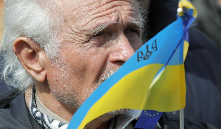 A man holds an Ukrainian flag as protesters gather to march to the Olympic stadium ahead of debates between two candidates in the weekend presidential run-off in Kiev, Ukraine, Friday, April 19, 2019. Friday is the last official day of election canvassing in Ukraine as all presidential candidates and their campaigns will be barred from campaigning on Saturday, the day before the vote. (AP Photo/Vadim Ghirda)