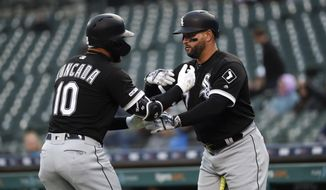 Chicago White Sox's Yoan Moncada (10) celebrates his solo home run with Yonder Alonso, against the Detroit Tigers during the first inning of a baseball game in Detroit, Friday, April 19, 2019. (AP Photo/Paul Sancya)