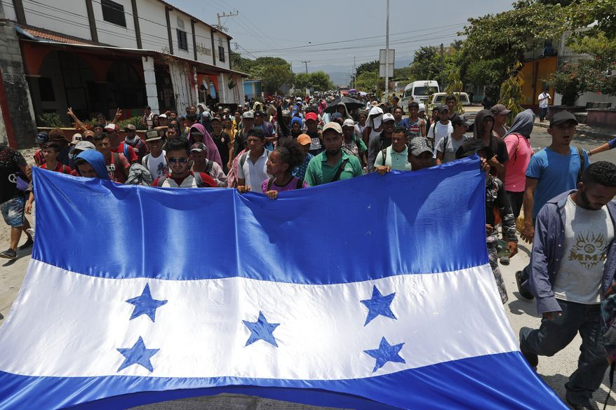 """In this file photo, Honduras migrants, part of a caravan hoping to reach the U.S. border, carry their national flag as they arrive to Mapastepec, Chiapas State, Mexico, Saturday, April 20, 2019. In a letter to Secretary of State Mike Pompeo dated April 22, House Foreign Affairs Committee Chairman Eliot Engel, New York Democrat, and Texas Rep. Michael McCaul, the panel's ranking Republican, said the Trump adminstration's plan to cut financial aid to Central Ameican countries like Honduras """"would be counterproductive and lead to increased migration flows to the U.S."""" (AP Photo/Moises Castillo)  **FILE**"""