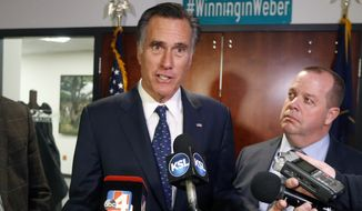 In this Friday, Jan. 18, 2019, file photo, Utah Sen. Mitt Romney, left, speaks with reporters after visiting with local officials to discuss how the four-week partial government shutdown is impacting an area with several major federal employers, including the Internal Revenue Service in Ogden, Utah. (AP Photo/Rick Bowmer, File)
