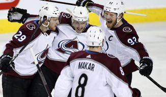 Colorado Avalanche left wing Gabriel Landeskog (92) celebrates his goal against the Calgary Flames with teammates Nathan MacKinnon (29), Tyson Barrie (4) and Cale Makar (8) during the first period of Game 5 of an NHL hockey first-round playoff series Friday, April 19, 2019, in Calgary, Alberta. (Larry MacDougal/The Canadian Press via AP)