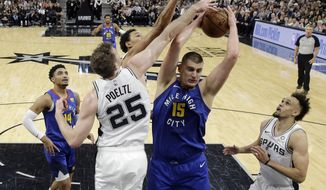 Denver Nuggets center Nikola Jokic (15) is defended by San Antonio Spurs center Jakob Poeltl (25) as he tries to score during the first half of Game 4 of an NBA basketball playoff series in San Antonio, Saturday, April 20, 2019. (AP Photo/Eric Gay)