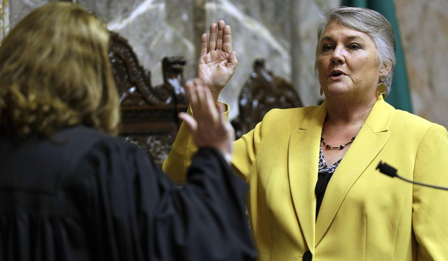 FILE - In this Jan. 9, 2017 file photo, Sen. Maureen Walsh, R-Walla Walla, right, takes the oath of office on the opening day of the 2017 legislative session at the Capitol in Olympia, Wash. Sen. Walsh has angered nurses by commenting in a speech that some nurses may spend a lot of time playing cards in rural hospitals. The Olympian reports that state Sen. Maureen Walsh, a Republican, made the comments this week while debating a Senate bill that would require uninterrupted meal and rest breaks for nurses. Walsh wants an amendment that would exclude hospitals with fewer than 25 beds. A Washington State Nurses Association blog about the comments drew so many readers Friday, April 19, 2019, that the site crashed. (AP Photo/Ted S. Warren, File)