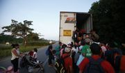 Central American migrants climb into the back of a tractor trailer as a thousands strong caravan makes its way north hoping to reach the U.S. border, between Pijijiapan and Tonala, Mexico, Friday, Oct. 26, 2018. Many migrants said they felt safer traveling and sleeping with several thousand strangers in unknown towns than hiring a smuggler or trying to make the trip alone.(AP Photo/Rebecca Blackwell)