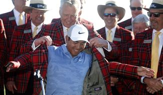 C.T. Pan puts on the traditional plaid jacket after winning the RBC Heritage golf tournament at Harbour Town Golf Links on Hilton Head Island, S.C., Sunday, April 21, 2019. Pan won with a 12-under par for his first PGA victory. (AP Photo/Mic Smith)