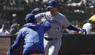 Toronto Blue Jays' Justin Smoak, right, is congratulated by a teammate after hitting a two-run home run against the Oakland Athletics during the seventh inning of a baseball game in Oakland, Calif., Sunday, April 21, 2019. (AP Photo/Jeff Chiu)