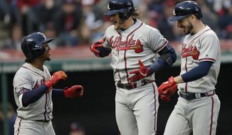 Atlanta Braves' Josh Donaldson, center, is congratulated by Ozzie Albies, left, and Matt Joyce after Donaldson hit a three-run home run in the second inning of a baseball game against the Cleveland Indians, Sunday, April 21, 2019, in Cleveland. Albies and Joyce scored on the play. (AP Photo/Tony Dejak)