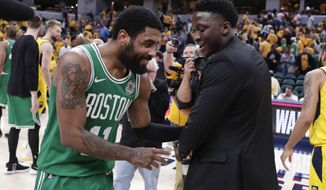Boston Celtics guard Kyrie Irving (11) isa congratulated by injured Indiana Pacers guard Victor Oladipo (4) following Game 4 of an NBA basketball first-round playoff series in Indianapolis, Sunday, April 21, 2019. The Celtics defeated the Pacers 110-106 to win the series 4-0. (AP Photo/Michael Conroy)