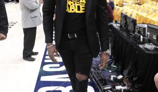 Injured Indiana Pacers guard Victor Oladipo (4) walks down the sideline during warmups before Game 4 of an NBA basketball first-round playoff series against the Boston Celtics in Indianapolis, Sunday, April 21, 2019. (AP Photo/Michael Conroy)