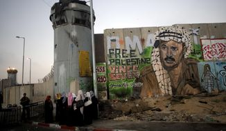 File - In this Friday, Aug. 13, 2010 file photo, Palestinian women wait near a section of Israel's separation barrier covered in graffiti, one depicting the late Palestinian leader Yasser Arafat, at the Qalandiya checkpoint , between Jerusalem and the West Bank city of Ramallah. Israel's election this month may have dimmed hopes for a two-state solution with the Palestinians as a way of resolving one of the Middle East's most intransigents conflicts. The vote, in which Prime Minister Benjamin Netanyahu coasted to another victory, left no doubt that peace talks with the Palestinians won't be on the agenda anytime soon. (AP Photo/Sebastian Scheiner, File)