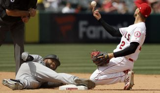 Los Angeles Angels shortstop Andrelton Simmons, right, tosses the ball after Seattle Mariners' Domingo Santana was tagged out trying to stretch a single into a double during the sixth inning of a baseball game in Anaheim, Calif., Sunday, April 21, 2019. (AP Photo/Chris Carlson)
