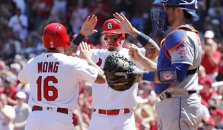 St. Louis Cardinals' Kolten Wong, left, and teammate Yadier Molina celebrate after scoring past New York Mets catcher Travis d'Arnaud, right, during the second inning of a baseball game Sunday, April 21, 2019, in St. Louis. (AP Photo/Jeff Roberson)