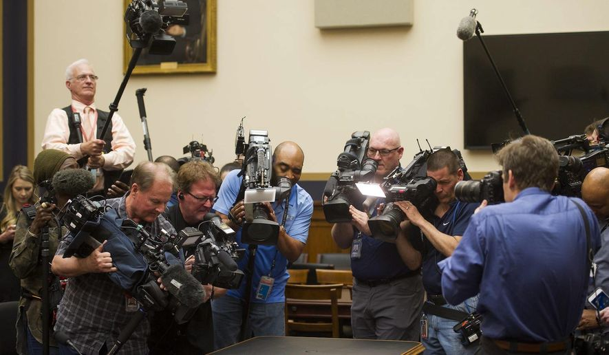 Photojournalists gather to snap images of four pages of the report by special counsel Robert Mueller placed on the witness table. (Associated Press)