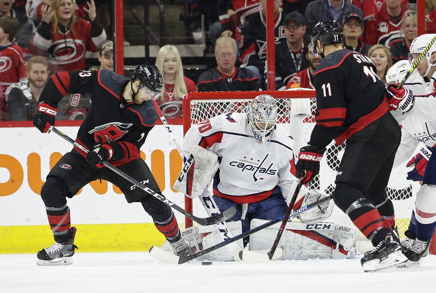 Carolina Hurricanes' Warren Foegele (13) tries to score against Washington Capitals goalie Braden Holtby (70) while Hurricanes' Jordan Staal (11) assists during the first period of Game 6 of an NHL hockey first-round playoff series in Raleigh, N.C., Monday, April 22, 2019. (AP Photo/Gerry Broome)