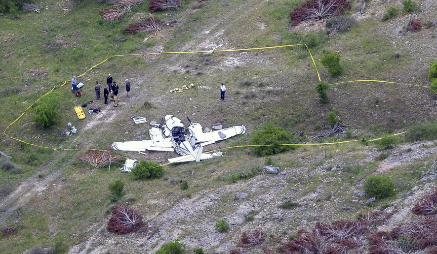 Authorities investigate at the crash scene of a twin-engine Beechcraft BE58, Monday, April 22, 2019, near Kerrville, Texas. The pilot and the five other people aboard the plane were all killed, said Sgt. Orlando Moreno, a spokesman for the Texas Department of Public Safety. (William Luther/The San Antonio Express-News via AP)