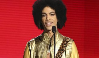 """FILE - In this Nov. 22, 2015, file photo, Prince presents the award for favorite album - Soul/R&B at the American Music Awards in Los Angeles. The memoir Prince was working on at the time of his death, """"The Beautiful Ones,"""" is due out in late October 2019. (Photo by Matt Sayles/Invision/AP, File)"""