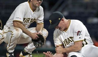 Pittsburgh Pirates relief pitcher Nick Burdi, right, holds his arm after delivering a pitch during the eighth inning of a baseball game against the Arizona Diamondbacks in Pittsburgh, Monday, April 22, 2019. Burdi left the game with a team trainer, and the Diamondbacks won 12-4. (AP Photo/Gene J. Puskar)