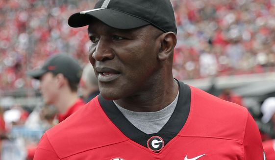 FILE - In this Oct. 27, 2019, file photo, former professional boxer Evander Holyfield paces the sidelines as he watches his son, Georgia running back Elijah Holyfield, play in an NCAA college football game against Florida, in Jacksonville, Fla. Elijah Holyfield says it wasn't an easy decision to leave Georgia after his junior season. (AP Photo/John Raoux, File)