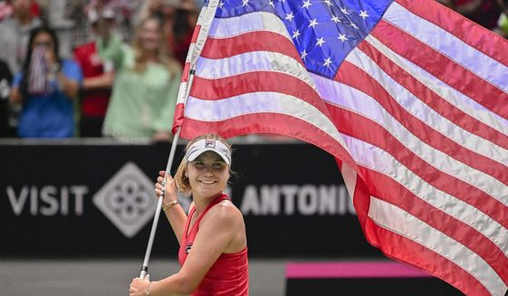 United States' Sofia Kenin carries the flag around the arena after winning a tie breaker against Switzerland's Timea Bacsinszky, after their playoff-round Fed Cup tennis match, Sunday, April 21, 2019, in San Antonio. (AP Photo/Darren Abate)