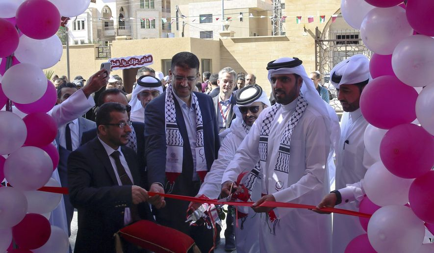 Khalifa al-Kuwari, second right, director of the Qatar Fund for Development, cuts the ribbon during the opening ceremony of new Sheikh Hamad bin Khalifa Al Thani Hospital for Rehabilitation and Artificial limbs in Gaza City, Monday, April 22, 2019. Qatar inaugurated the Gaza Strip's first prosthetic hospital and disability rehab center after many delays. Health officials say the 100-bed hospital is vital for Gaza, where more than 130 Palestinians have lost limbs over the past year during ongoing protests along Gaza-Israel perimeter fence. (AP Photo/Adel Hana)
