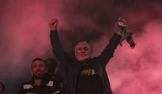 PAOK chairman Ivan Savvidis celebrates with fans the Greek Super League championship title in front of the White Tower, in Thessaloniki, northern Greece, early Monday, April 22, 2019. PAOK won the Greek league with a round to spare after beating Levadiakos 5-0, 34 years after the last time the team won the championship. (AP Photo/Giannis Papanikos)