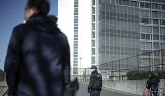 FILE - In this Jan. 11, 2019, file photo,  a security official, center, stands guard in front of Tokyo Detention Center, where former Nissan chairman Carlos Ghosn is detained, in Tokyo. Japanese media reported Monday, April 22, 2019 that Ghosn was indicted on new breach of trust charges. (AP Photo/Eugene Hoshiko, File)