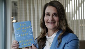 """In this photo taken Thursday, April 18, 2019, Melinda Gates poses for a photo with her new book, """"The Moment of Lift,"""" in Kirkland, Wash. Her new book is a memoir from the former Microsoft tech business executive, outspoken feminist and public supporter of the #MeToo movement. The Associated Press reviewed an advanced copy of the book ahead of its release Tuesday. (AP Photo/Elaine Thompson)"""