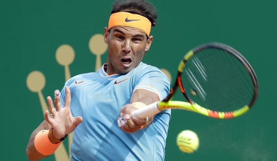 Spain's Rafael Nadal returns the ball toItaly's Fabio Fognini during their semifinal match of the Monte Carlo Tennis Masters tournament in Monaco, Saturday, April, 20, 2019. (AP Photo/Claude Paris)