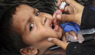 A health worker gives a polio vaccination to a child in Lahore, Pakistan, Monday, April 22, 2019. A Pakistani health official says the country has kicked off a nationwide polio vaccination campaign for the year in efforts to eradicate the crippling disease by the end of 2019. Pakistan reported only eight new polio cases in 2018. (AP Photo/K.M. Chaudary)