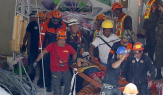 Rescuers carry an earthquake survivor after being pulled out from the rubble of a commercial building following Monday's 6.1 magnitude earthquake in Porac township, Pampanga province, north of Manila, Philippines, Tuesday, April 23, 2019. The strong earthquake struck the northern Philippines Monday trapping some people in a collapsed building, damaged an airport terminal and knocked out power in at least one province, officials said. (AP Photo/Bullit Marquez)