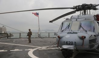 In this April 20, 2019, file photo, a U.S. marine patrols on the deck of the USS Blue Ridge, flagship of the U.S. Seventh Fleet, during a port call in Hong Kong, Saturday, April 20, 2019. (AP Photo/Kin Cheung, File)