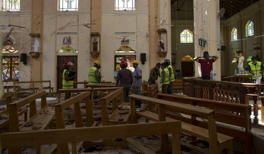 Investigators at the scene of a suicide bombing at St. Sebastian Church in Negombo, Sri Lanka, Monday, April 22, 2019. Easter Sunday bombings of churches, luxury hotels and other sites was Sri Lanka's deadliest violence since a devastating civil war in the South Asian island nation ended a decade ago. (AP Photo/Gemunu Amarasinghe)