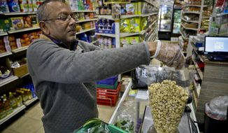 """Dhannitha Meemanage, from Sri Lanka, bags cashews in his family's grocery store, in New York's Staten Island's """"Little Sri Lanka"""" community, Monday, April 22, 2019. Sri Lanka's abrupt shutdown of social media sites in the wake of the string of deadly Easter Sunday terror attacks has left worried friends and relatives in places like """"Little Sri Lanka"""" in the dark. Meemanage, turned to old-fashioned means of getting news about loved ones after the attack, a landline phone. (AP Photo/Bebeto Matthews)"""