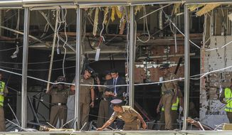 In this Sunday April 21, 2019, photo, a Sri Lankan Police officer inspects a blast spot at the Shangri-la hotel in Colombo, Sri Lanka. Sri Lankan authorities blame seven suicide bombers of a domestic militant group for coordinated Easter bombings that ripped through Sri Lankan churches and luxury hotels which killed and injured hundreds of people. It was Sri Lanka's deadliest violence since a devastating civil war in the South Asian island nation ended a decade ago. (AP Photo/Chamila Karunarathne, file)