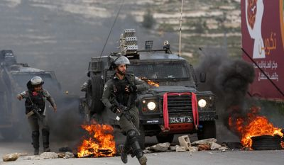 Israeli border policemen move away from a burning vehicle during clashes with Palestinians at checkpoint Bet El near the West Bank city of Ramallah , Wednesday, March 27, 2019.(AP Photo/Majdi Mohammed)