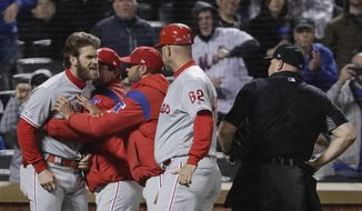 Philadelphia Phillies' Bryce Harper, left, is restrained while arguing with umpire Mark Carlson, right, during the fourth inning of a baseball game against the New York Mets, Monday, April 22, 2019, in New York. (AP Photo/Frank Franklin II) **FILE**