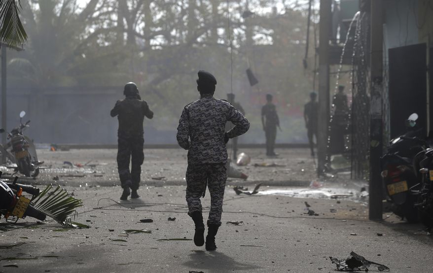 Sri Lankan security forces approach the site after a vehicle parked near St. Anthony's shrine exploded in Colombo, Sri Lanka, Monday, April 22, 2019. Easter Sunday bombings that ripped through churches and luxury hotels killed more than 200 people.(AP Photo/Eranga Jayawardena)