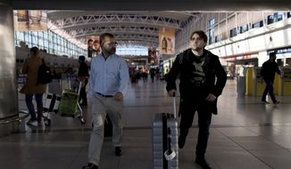 Tomas Ruiz pushes his suitcase as he is accompanied by his father Pablo at the International Airport Ministro Pistarini before boarding a plane to Ireland, in Ezeiza, Argentina, Thursday, April 4, 2019. Ruiz holds a European passport by descent, and is returning to the home country of his grandparents, far from Argentina's sizzling inflation, high unemployment and sharp currency depreciation. (AP Photo/Tomas F. Cuesta)