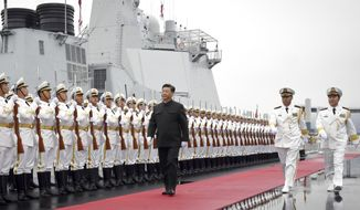 In this photo released by Xinhua News Agency, Chinese President Xi Jinping reviews an honor guard before boarding the destroyer Xining at a pier in Qingdao, east China's Shandong Province, Tuesday, April 23, 2019. Xi urged closer ties between the world's navies on Tuesday, amid tensions over China's rapid expansion of its naval forces and forceful assertions of territorial claims in the South China Sea. (Li Gang/Xinhua via AP)